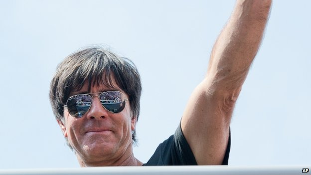 German national soccer coach Joachim Loew waves to fans after the arrival of the German soccer squad in Berlin