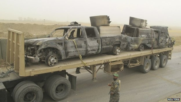 Burned-out vehicles are transported by the Iraqi military in Salahuddin province (15 July 2014)