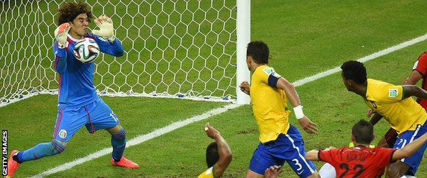 Mexico goalkeeper Guillermo Ochoa saves a header from Brazil's Thiago Silva
