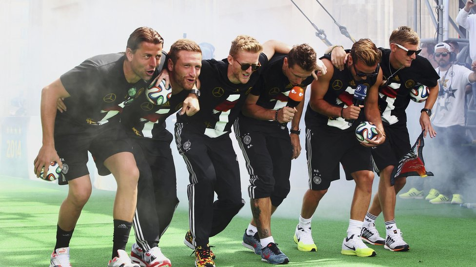 """Germany's Roman Weidenfeller, Shkodran Mustafi, Andre Schuerrle, Miroslav Klose, Mario Goetze and Toni Kroos (L-R) appear on stage during celebrations to mark the team's 2014 Brazil World Cup victory, at a """"fan mile"""" public viewing zone in Berlin on 15 July 2014."""