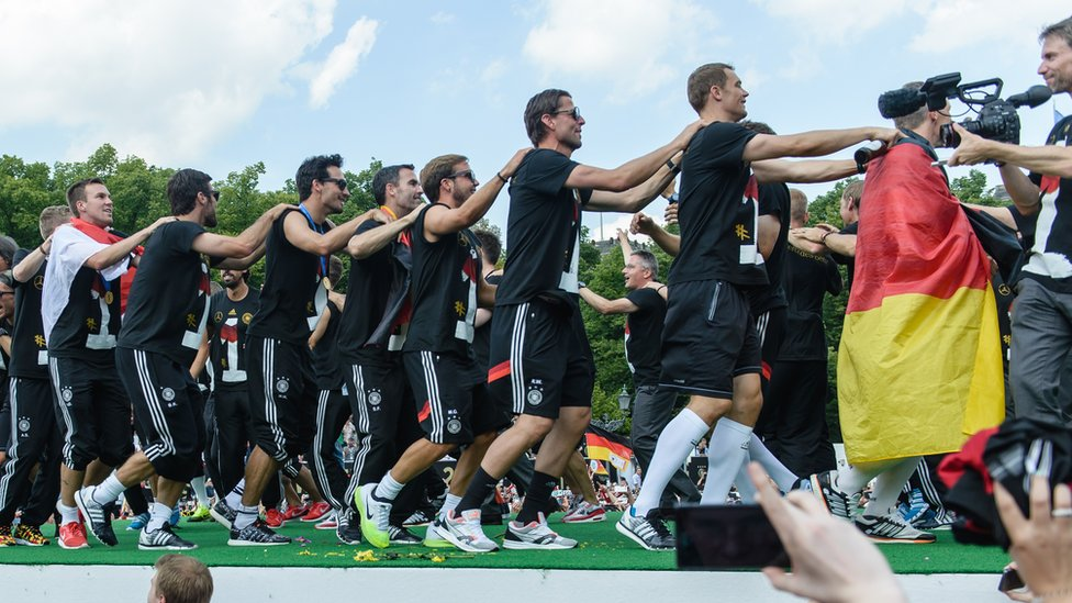 Germany's players perform a conga line during a victory parade of Germany's football national team on 15 July 2014 at Berlin's landmark Brandenburg Gate