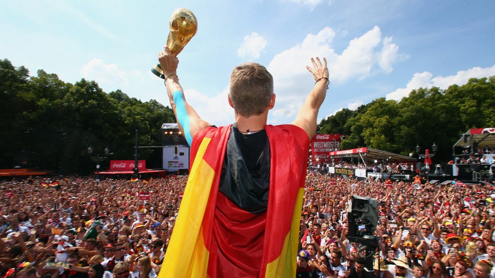 Bastian Schweinsteiger celebrates on stage at the German team victory ceremony on 15 July 2014 in Berlin, Germany.