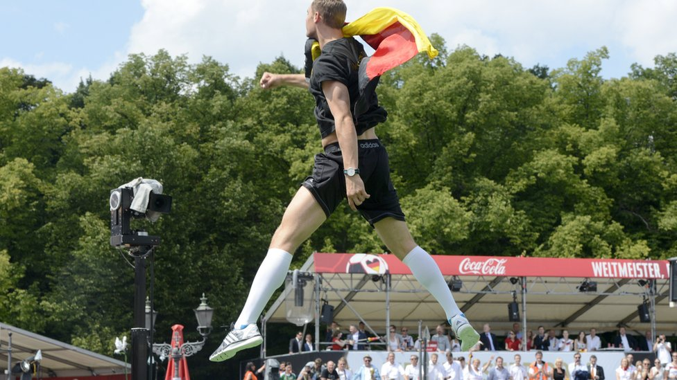 German goalkeeper Manuel Neuer jumps on the stage in front of fans for their victory parade on 15 July 15, 2014 at Berlin's landmark Brandenburg Gate