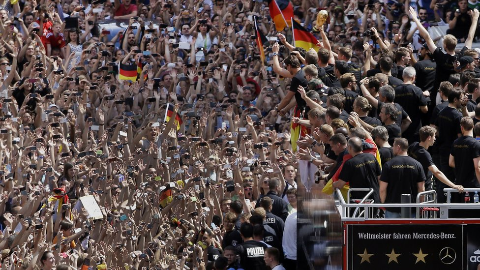 Members of the German football team wave to fans after the arrival of the German national soccer team in Berlin on 15 July 2014