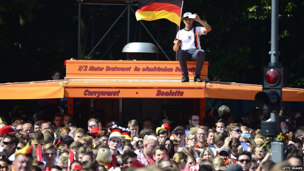 German fans await the arrival of the German national team at Berlin's landmark Brandenburg Gate to celebrate their FIFA World Cup title on 15 July 2014