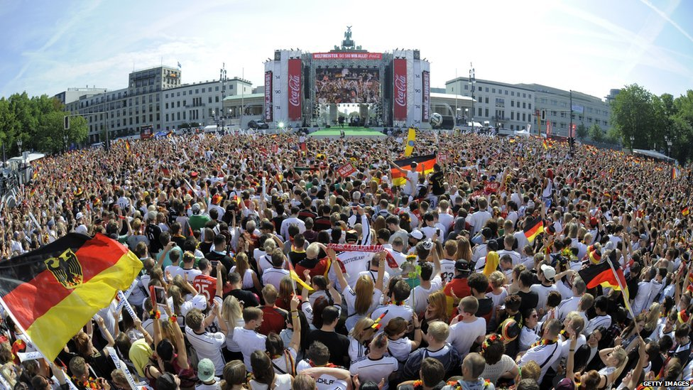 An overview taken with a fisheye lens shows German fans gather in front of a stage installed for a victory parade of Germany's football national team on 15 July 2014 at Berlin's landmark Brandenburg Gate