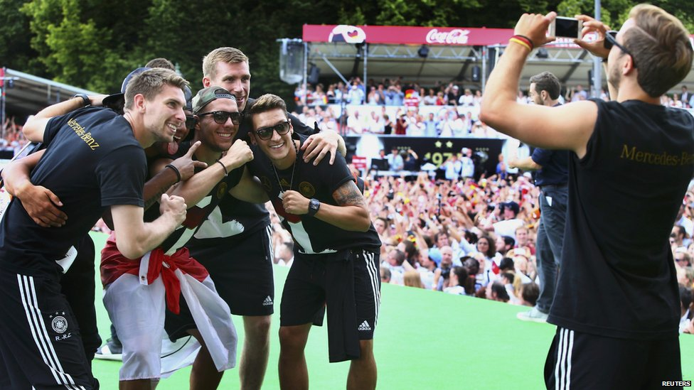 Germany's Mario Goetze (R) takes a photo of fellow team mates during celebrations to mark the team's 2014 Brazil World Cup victory in Berlin on 15 July 2014.
