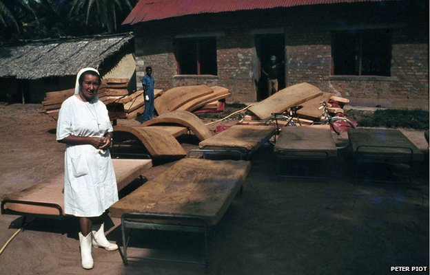 A nun standing beside beds in Yambuku, 1976