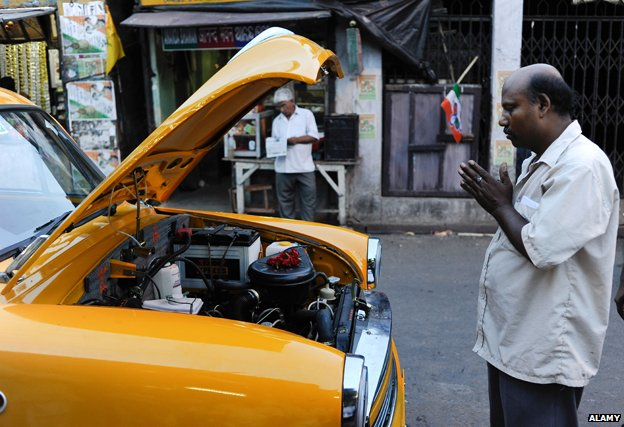 Man blesses his Ambassador taxi