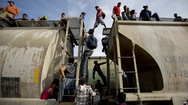 Central American migrants climb a train in Ixtepec, Mexico