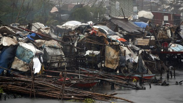 Squatter homes partially destroyed by strong winds brought by Typhoon Rammasun are pictured as it hit the coastal town of Bacoor, Cavite southwest of Manila on 16 July, 2014