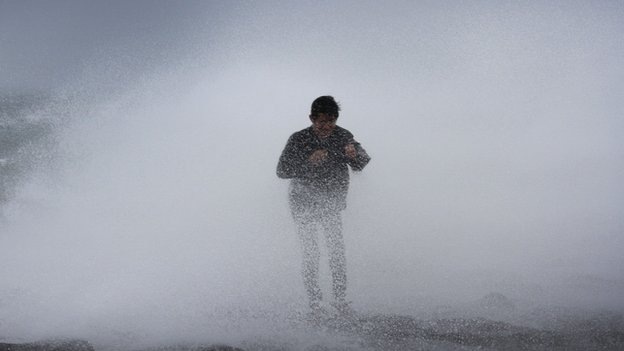 A resident stands near waves in Legazpi City, southeast of Manila, on 15 July, 2014 as authorities warned of approaching Typhoon Rammasun