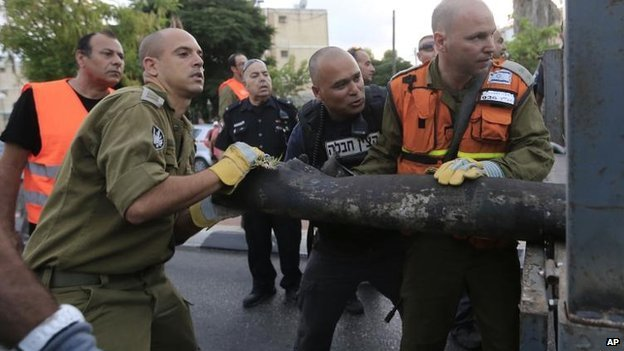 Israeli security forces remove the remains of a rocket fired at the city of Ashkelon, 15 July