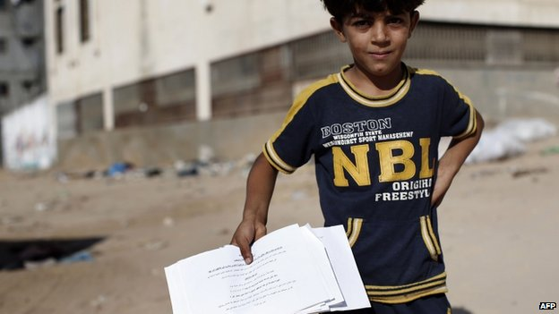 Palestinian boy holds up a leaflet in Gaza City (16 July 2014)