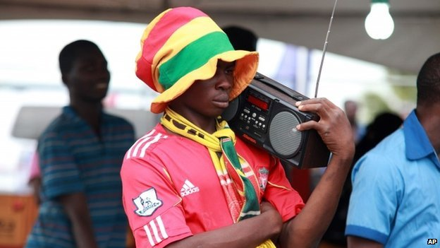 A Ghanaian fan listens to live commentary on the radio at the soccer village in Accra, Ghana as others watch the Ghana Portugal Group G FIFA World Cup 2014 preliminary round soccer match taking place in Brazil on a public screen