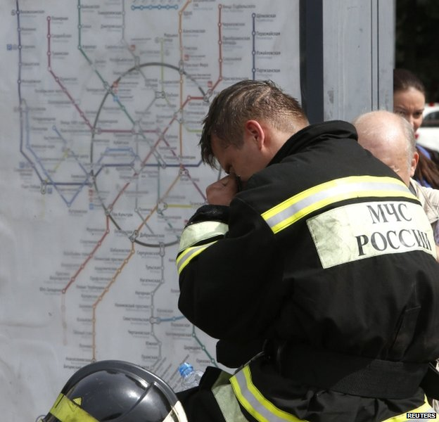 A rescue worker rests beside a map of the metro in Moscow, 15 July