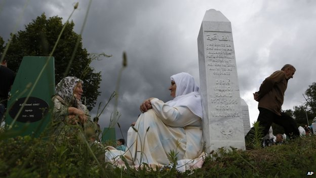 Bosnian Muslim women rest near a gravestone during a funeral in Srebrenica, Bosnia on 11 July  2014.