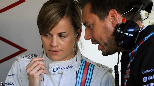 William's Susie Wolff talks to mechanics in the garage before the first practice session at the British Grand Prix
