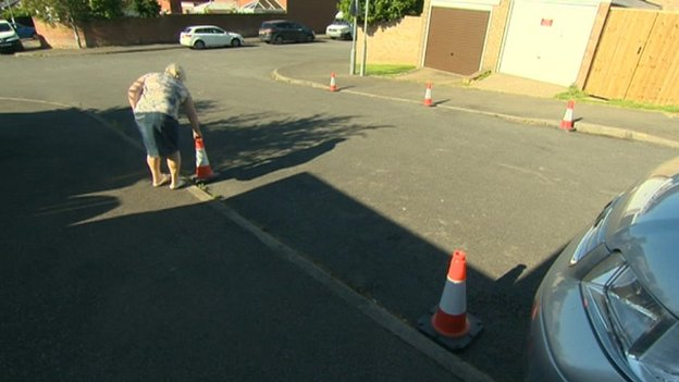 Woman putting traffic cones on road in Wellingborough