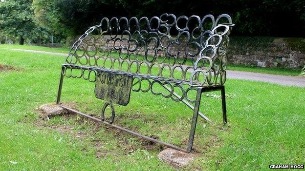 Situated overlooking the village green and duck pond, the bench is constructed largely of horseshoes.
