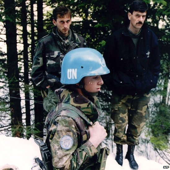 A Dutch UN peacekeeper standing near two unidentified Bosnian men in Srebrenica (1994)
