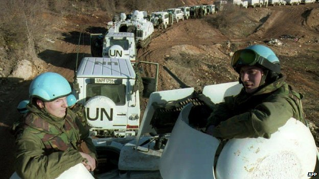 Dutch soldiers riding on an armoured vehicle accompanying a Dutch-UN convoy of 56 engineering vehicles on their way to Lukavac in Bosnia-Hercegovina (February 1994)