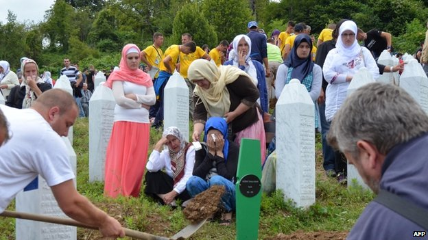 Bosnian Muslims, family members and survivors of the Srebrenica 1995 massacre, attend the burial ceremony at a memorial cemetery in Potocari near Srebrenica (11 July, 2014)