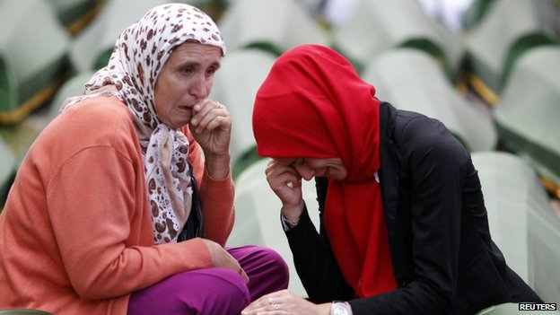 Bosnian Muslim women alongside the coffin of a relative, one of the 175 coffins of newly identified victims from the 1995 Srebrenica massacre, in Potocari Memorial Centre near Srebrenica (14 July 2014)