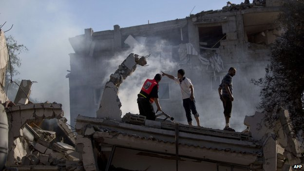 Palestinian fire fighters and residents tried to extinguish a fire at a house destroyed by an overnight Israeli air strike in Gaza City on 16 July 2014