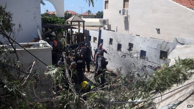 Emergency workers and Israeli security check a house damaged by a rocket fired by militants from Gaza on July 16, 2014, in the city of Ashkelon
