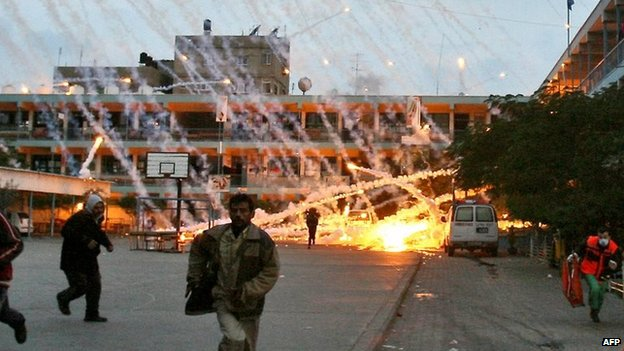 Palestinians run during an Israeli strike at a UN school in Beit Lahya, northern Gaza, on 17 January 2009