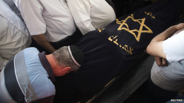 Relatives of Dror Khenin mourn next to his body during his funeral nea Tel Aviv, after Mr Khenin was killed on Tuesday (16 July 2014)