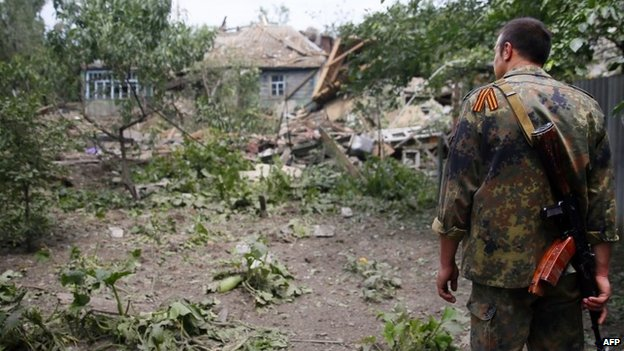 A pro-Russian militant  looks at a destroyed house in Snizhne, eastern Ukraine