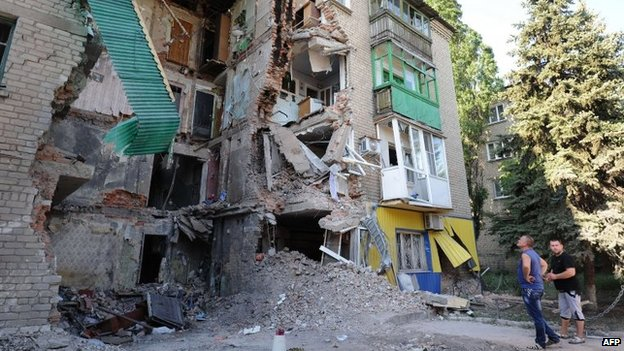 Men look at a building destroyed by the Ukrainian Air Force in Snezhnoye, 80 km east of Donetsk, on July 16