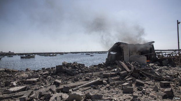 Palestinian children killed by Israeli naval bombardment in Gaza port: Smoke rises from a shed in the port of Gaza City where five young boys were killed by an Israeli naval bombardment (16 July 2014)