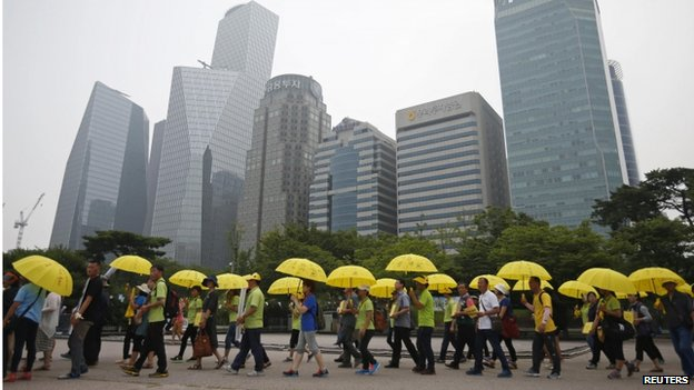 People holding yellow umbrellas in support of victims of the mid-April Sewol ferry disaster, carry boxes containing signatures of South Koreans petitioning for the enactment of a special law after the disaster, as they march towards the National Assembly at Yeouido Park in Seoul on 15 July 2014.