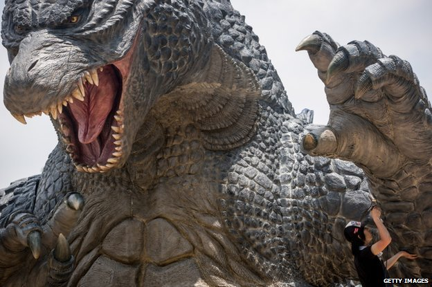 A man airbrushes the final touches to a 6.6 meter replica of the famous Godzilla at Tokyo