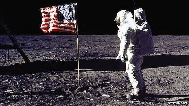 Buzz Aldrin stands near a US flag on the surface of the moon.