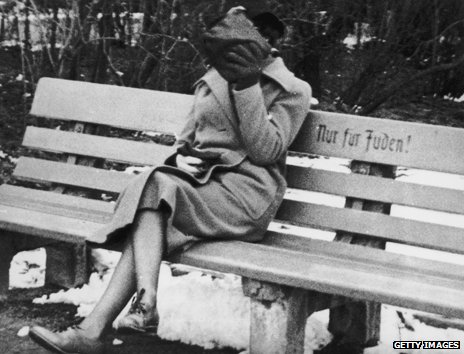 "c.1938: A woman hides her face as she sits at a bench marked ""Nur fur Juden"", meaning ""for Jews only"""