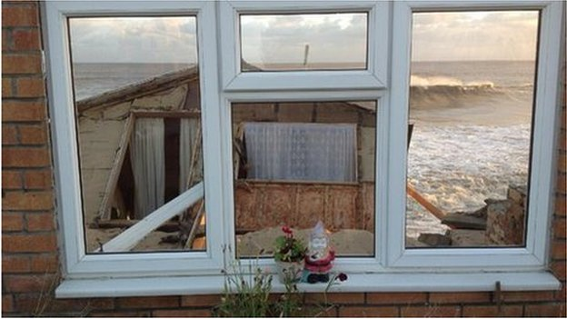 The sea seen through the front windows of a beach chalet - the rest of which has collapsed