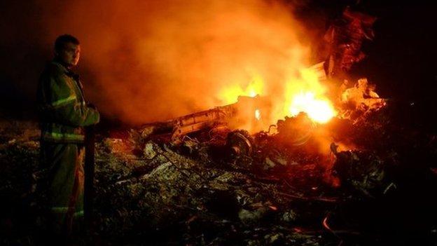 Un vigile del fuoco si pone come fiamme scoppiare tra i relitti di aereo malese portando 298 persone provenienti da Amsterdam a Kuala Lumpur dopo che è caduto, vicino alla città di Shaktarsk, in mano ai ribelli est Ucraina, il 17 luglio 2014
