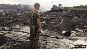 An armed pro-Russian separatist stands at a site of a Malaysia Airlines Boeing 777 plane crash in the settlement of Grabovo in the Donetsk region on 17 July 2014.