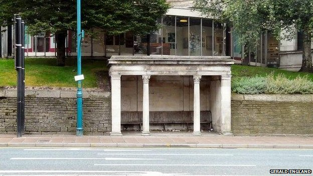 A stone shelter with wooden benches on Wellington Road South. Behind it is Stockport Art Gallery.