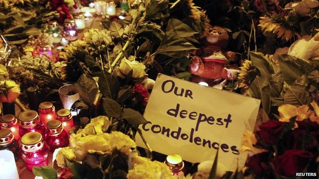 A message of condolence is left among candles and flowers near the Dutch embassy for victims of Malaysia Airlines MH17, which crashed in eastern Ukraine, in Kiev on 17 July 2014