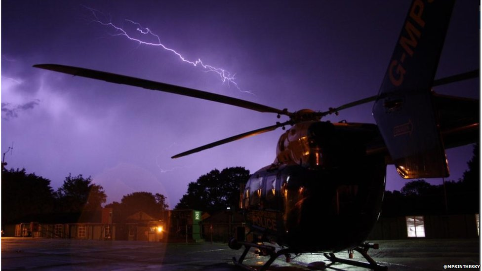 Lightning seen in the sky over a police helicopter which is on the ground