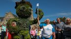 Baton bearer poses next to three metre high shrub pruned to resemble Commonwealth Games mascot Clyde
