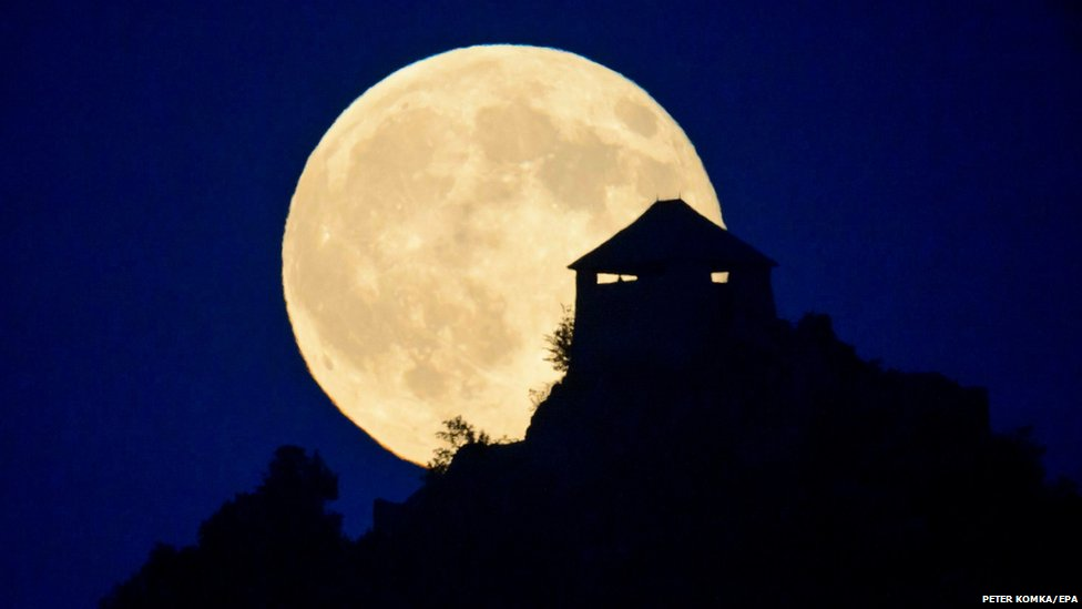 A full moon rises above the castle of Somoskoujfalu, Budapest, Hungary