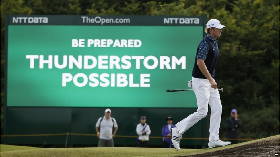 "Golfer Brandt Snedeker walks past a sign which says: ""Be prepared. Thunderstorm possible."""