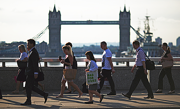 People walking on a bridge with Tower Bridge in the background