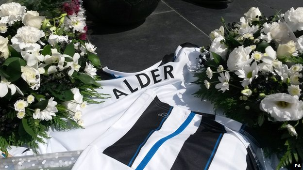 Flowers and football shirts outside St James Park